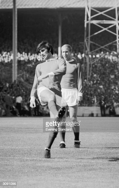 Manchester United's George Best on the football field with Bobby Charlton behind him