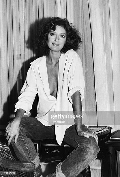 Portrait of American actor Susan Sarandon sitting on a desk with her shirt unbuttoned to reveal her cleavage Warwick Hotel New York City