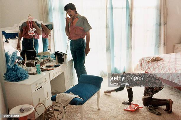 A 14year old domestic servant cleans the carpet as Johan Richter an Afrikaner farmer from Free State talks on his bedroom telephone