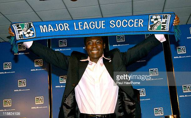 Year old Freddy Adu holds up a Major League Soccer banner during a news conference announcing his multi year deal with Major league Soccer at Madison...