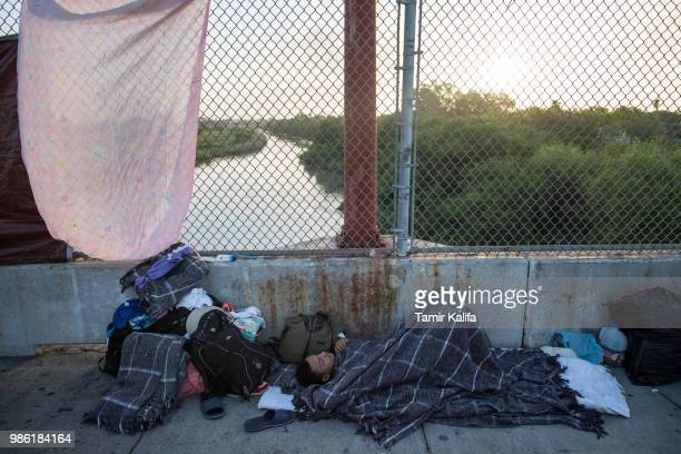 A 14yearold boy from Honduras sleeps on the Mexican side of the Brownsville Matamoros International Bridge where he and his family have been waiting...