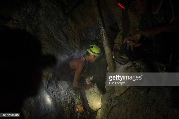 A 14yearold gold miner prepares to heft a sack of raw ore onto his back before carrying it to a processing station on the surface on April 22 2014 in...