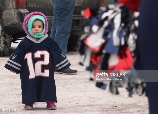 15monthold Makenna King wearing a Tom Brady jersey looks at the pom pom of New England Patriots cheerleader Michaela Main at Bug Light Park in South...