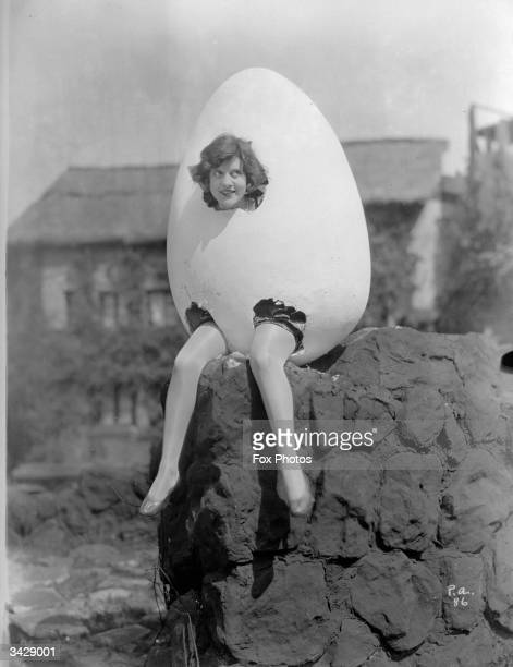 Dorothy Gulliver wears an egg costume and perches on a wall as in the nursery rhyme 'Humpty Dumpty'