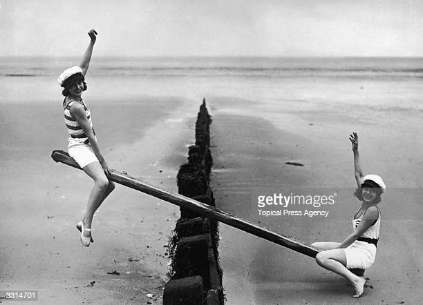 Two women playing on their home-made see-saw, on a beach breakwater.