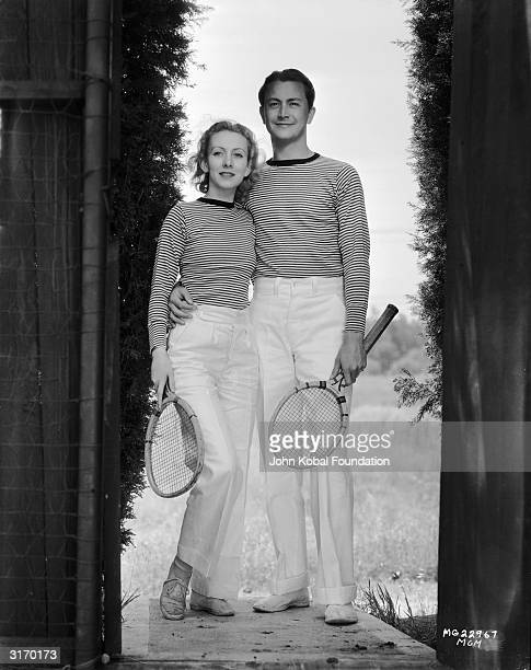 American actor Robert Young with his girlfriend actress Karen Morley in their matching tennis outfits
