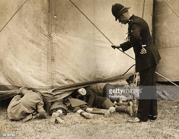 A policeman talking to a group of boys who are sneaking a look at the rehearsals of the Bertram Mills Tenting Circus at Luton