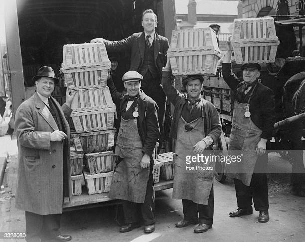 Covent Garden market porters carrying crates of tomatoes on their heads