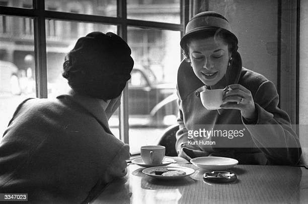 Two fashion models eating biscuits and smoking in the Buttery in Conduit Street London Original Publication Picture Post 5010 The Models Come Out For...