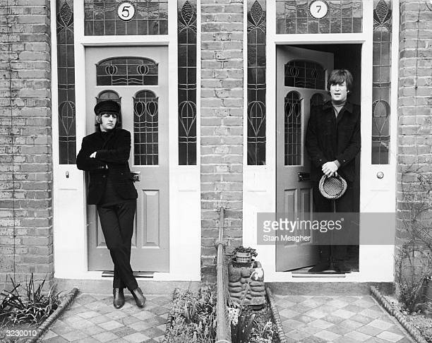 British musicians Ringo Starr and John Lennon members of the rock group The Beatles stand in the doorways of the adjoining suburban houses on Ailsa...