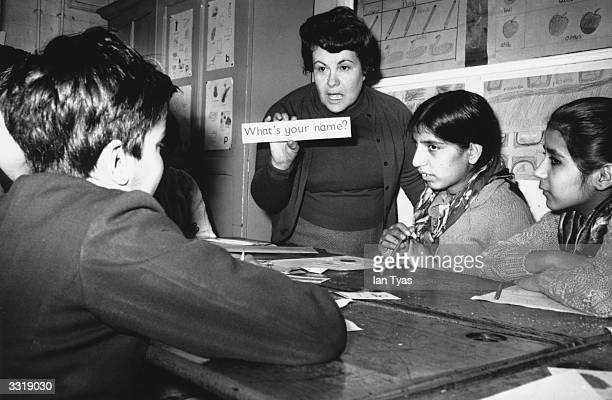 Teacher giving English lessons to immigrant children from India and Pakistan at a school in Walsall, Staffordshire.