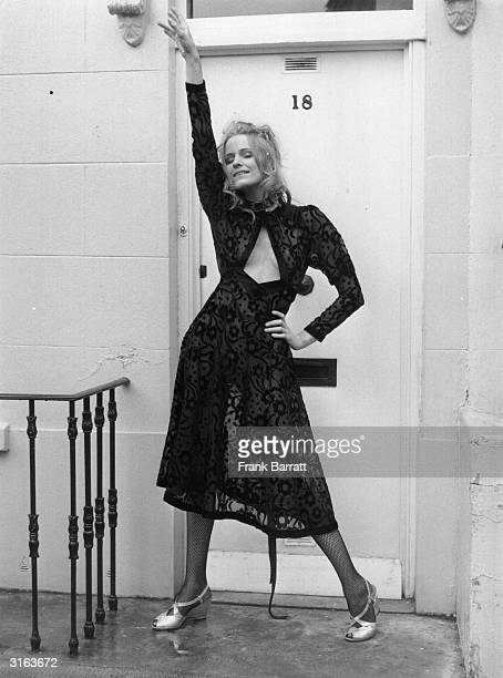 A black seethrough mididress with a keyhole neckline worn with fish net tights and silver sandals with wedge heels From a collection of April Fashion...