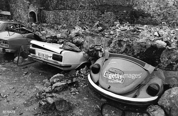 Cars crushed by a fallen brick wall destroyed in an earthquake in Budva Yugoslavia which killed hundreds and made thousands homeless