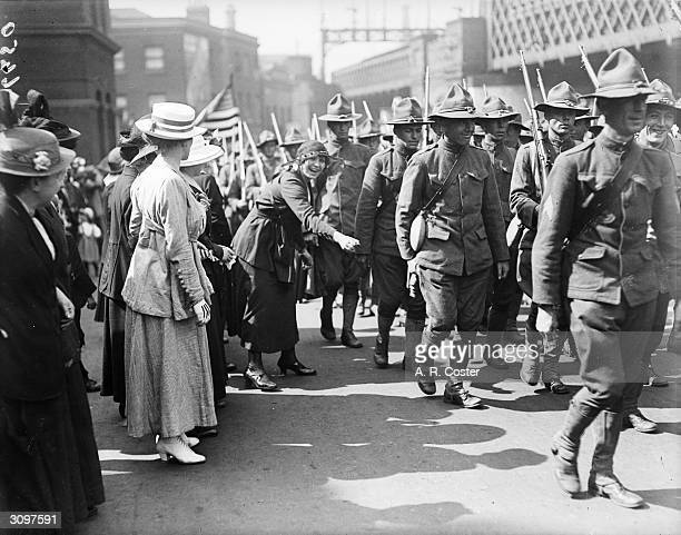 A woman cheers on a troop of American soldiers as they parade through the streets of London
