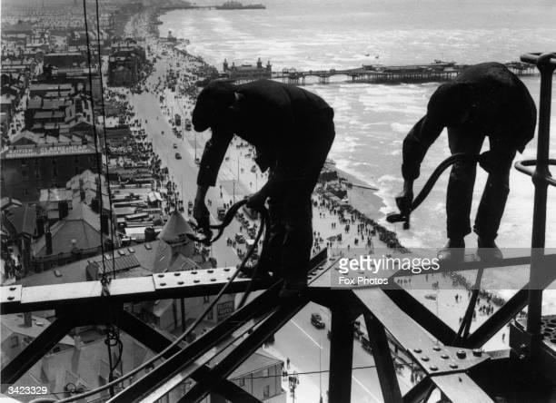 Balancing on girders high above the promenade workmen repair Blackpool Tower.