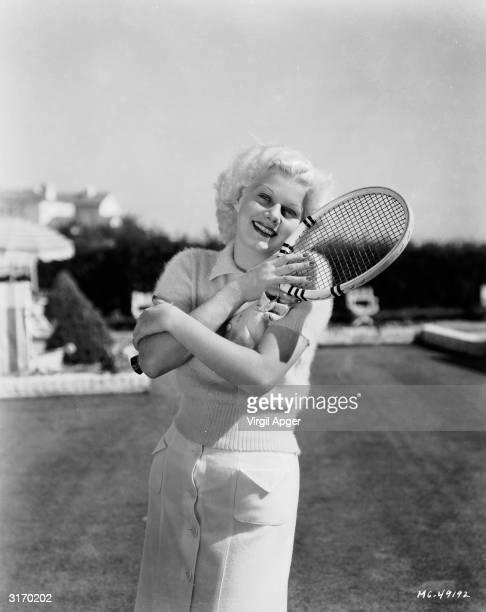 Star Jean Harlow hugging her tennis racquet.