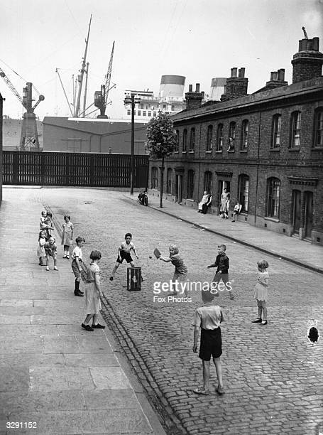 Children playing cricket in a street in Millwall east London A liner on the Thames is in the background