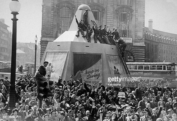 A few minutes after the Japanese surrender was announced Piccadilly Circus was filled with a jubilant crowd some of whom climbed on the plinth of the...