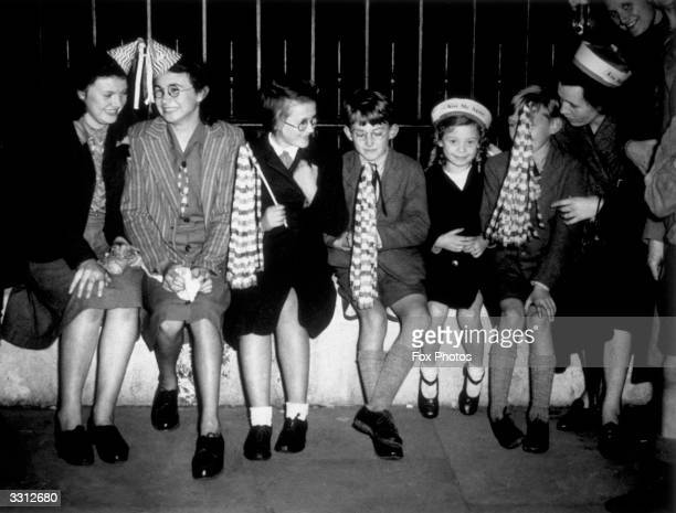 A party of youngsters wait on the railings of Buckingham Palace for news of the victory in the Far East