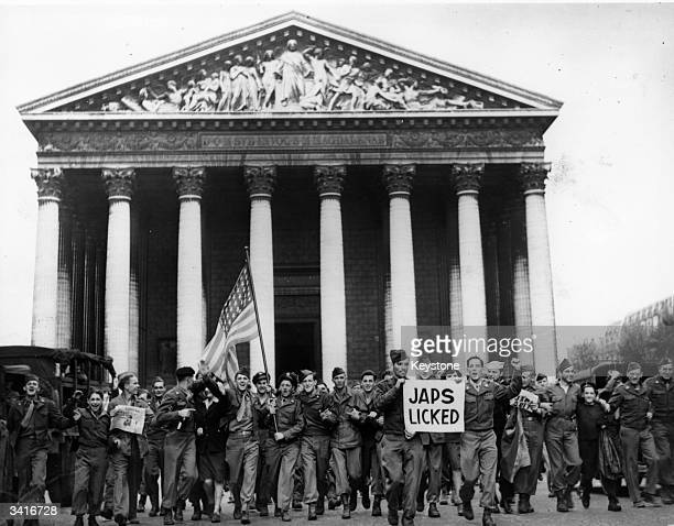 American troops in Paris celebrate news of the Japanese surrender by marching through the streets with the stars and stripes and a news headline that...