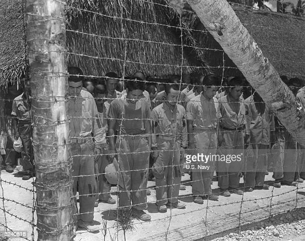 Fulllength image of Japanese POWs standing in rows with their heads bowed behind a barbed wire fence in an Allied internment camp during World War II...