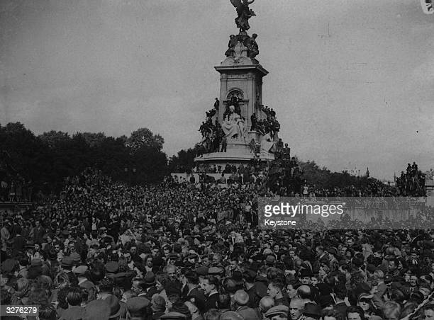 Huge crowds surround Queen Victoria's monument outside Buckingham Palace waiting to see the King on VJ Day