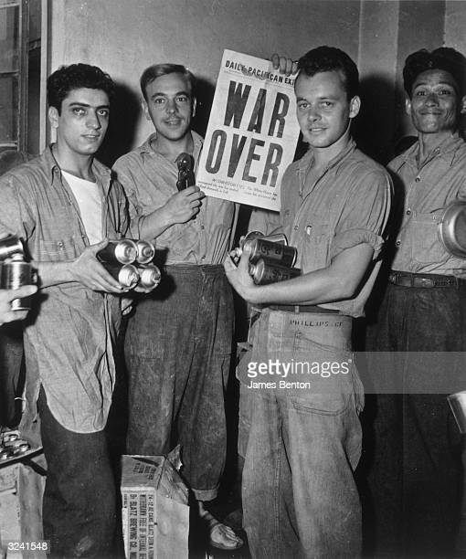 Men at a naval base were given four cans of beer each in celebration of the end of the World War II, Manila, Philippines. One of the men holds a 'WAR...