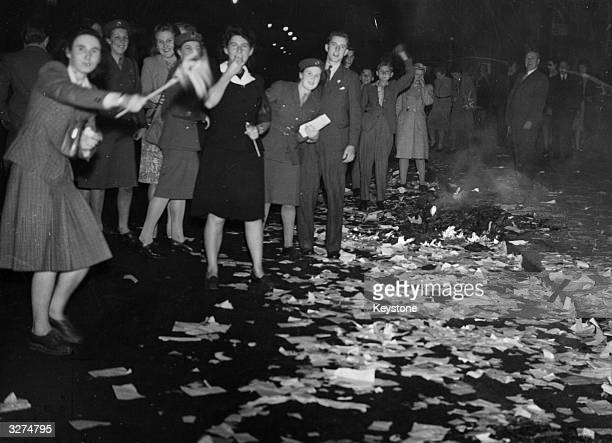 Paper littering the streets of London's West End after earlier celebrations by office workers at the news of Japan's surrender provides fuel for...