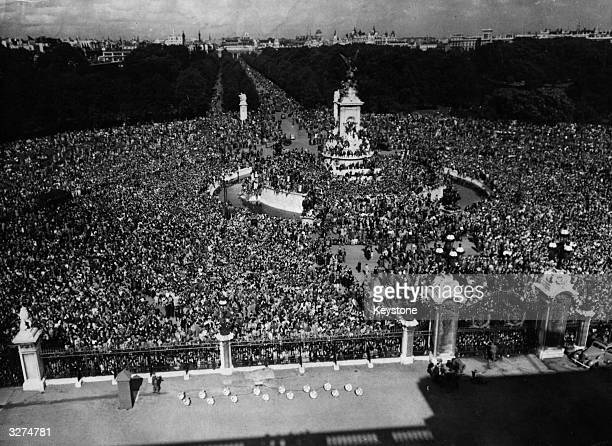 The view which greeted the King from Buckingham Palace on VJ Day. As far as the eye can see jubilant crowds stretch from Queen Victoria's monument...