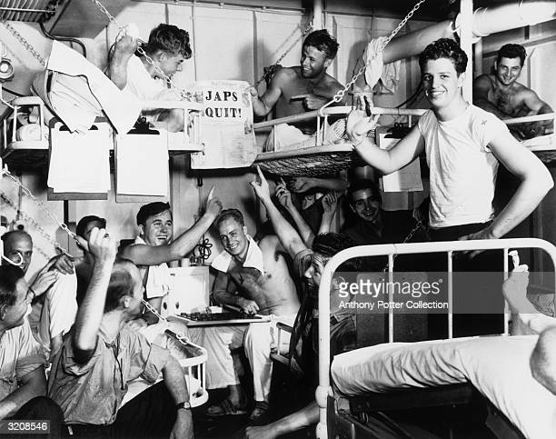 Servicemen in the sick bay of the S.S. Casablanca smile and point to a newspaper with the headline 'JAPS QUIT!', after the Japanese surrender in...