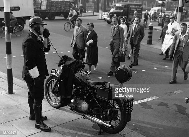 A police motorcyclist gives safetyfirst instructions to pedestrians at Kennington Oval in a drive to cut London's road casualties and keep the...