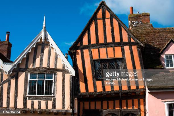 15th century crooked house antiques shop and tearooms in quaint wonky crooked orange timbered building in high street, lavenham, suffolk, england, uk. - lavenham fotografías e imágenes de stock