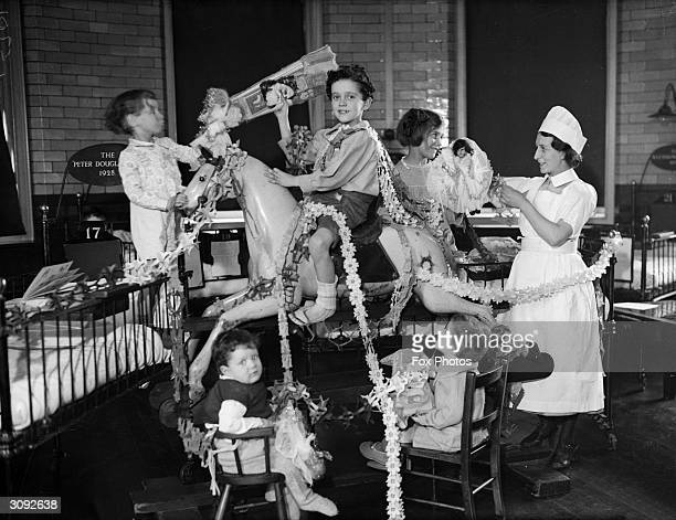 Children at the Great Ormond Street Hospital in London play with a mound of presents before Christmas