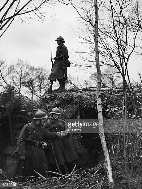 Fulllength of image of two Belgian soldiers standing in front of an underground fort reading a letter while a third soldier stands guard above them...