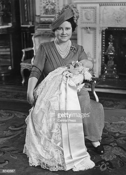 Queen Elizabeth holding Prince Charles her first grandchild who is wearing the Royal family christening gown after being baptised at Buckingham Palace