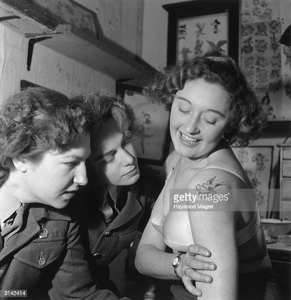 Two servicewomen admiring a tattoo by the Aldershot tattoo artist Jessie Knight the only female tattooist at work Original Publication Picture Post...