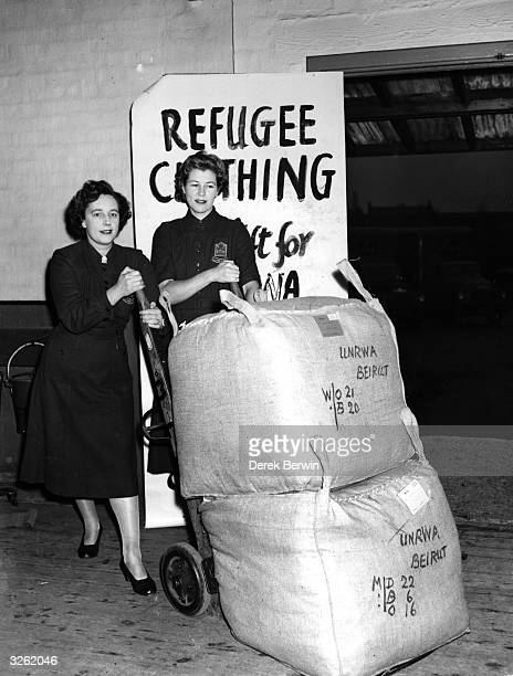Pamela Sutherland and Rita Penny wheel bales of clothing away from the baling department of the Women's Voluntary Service Clothing Depot to be sent...