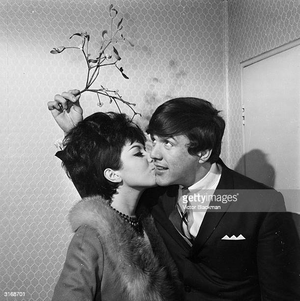 British musician Dave Clark of the Dave Clark Five kisses singer Susan Maughan under the mistletoe on his 21st birthday