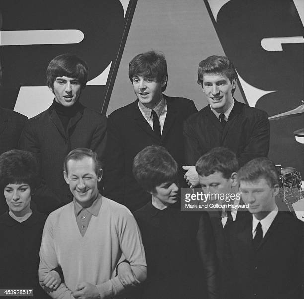 George Harrison and Paul McCartney from the Beatles pose with various members of the Searchers and the Breakaways and broadcaster Brian Matthew on...
