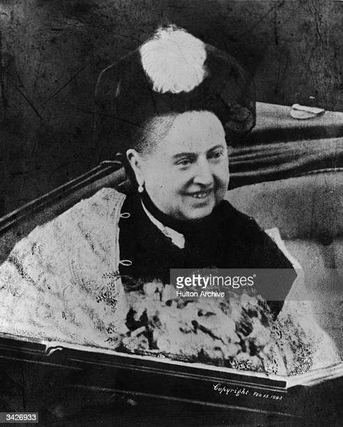 A smiling Queen Victoria in an open coach