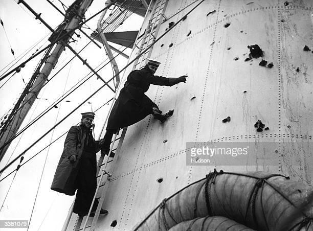 Naval officers examining the damaged forward stack of the HMS Exeter on its arrival at Plymouth The ship was damaged during a battle with the German...