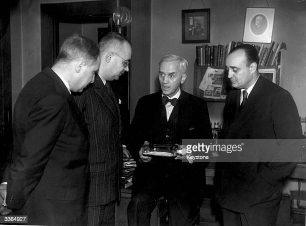 Bacteriologist Sir Alexander Fleming explains the theory of the production of penicillin from the bottle of mould he is holding to three Turkish...