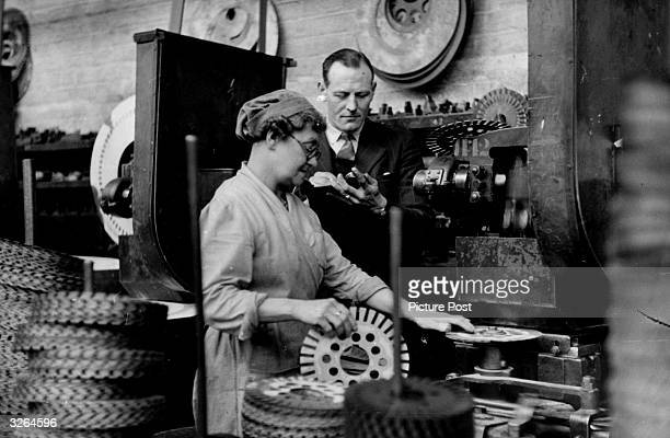 Supervisor checks a female employee's performance against a stopwatch in a time and motion study to try to improve production. Original Publication:...
