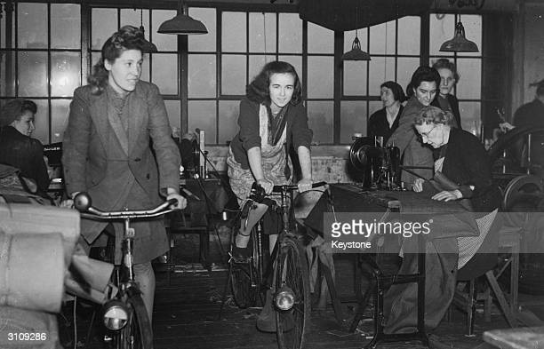 At a tent and tarpaulin factory in postwar Mile End east London machines are kept running on bicycle power during electricity cuts