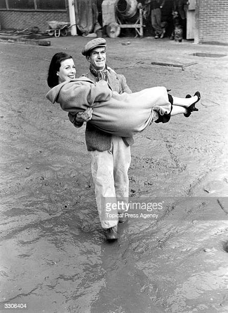 Constance Smith the film and stage star who appeared in 'House on the Square' is given a helping hand over the mud at the Festival of Britain site on...