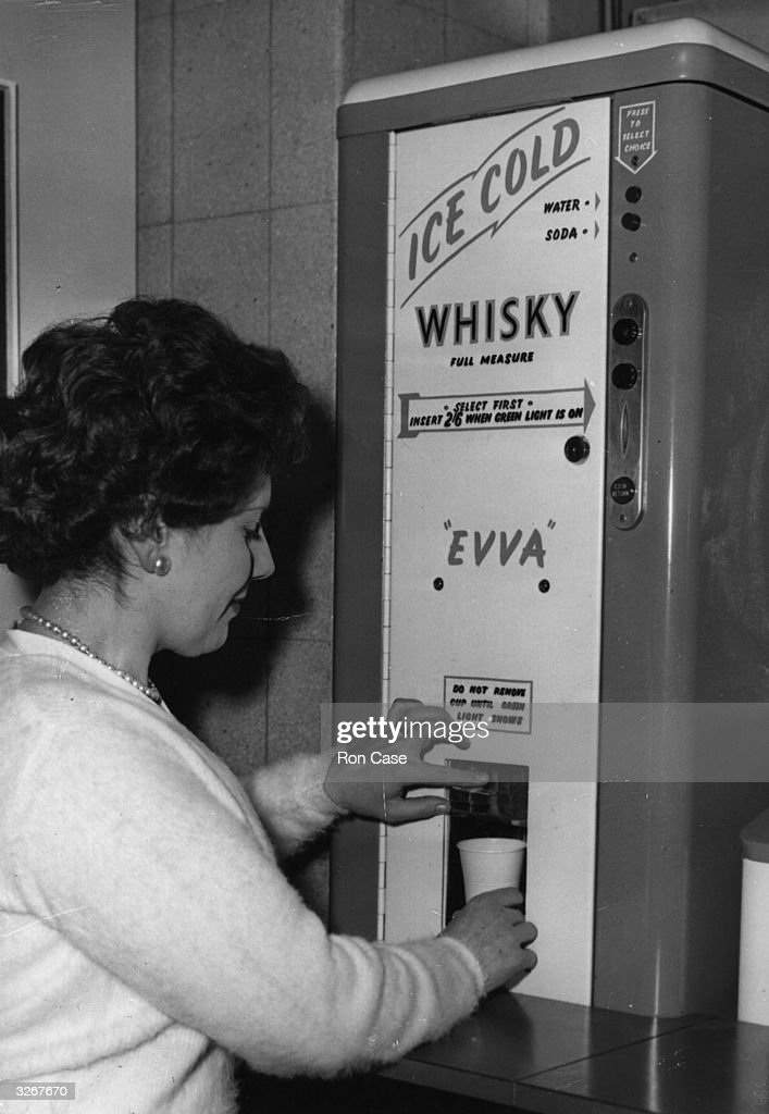 At the Second Automatic Vending Exhibition in London, a woman helps herself to a vending machine-mixed whisky and soda.