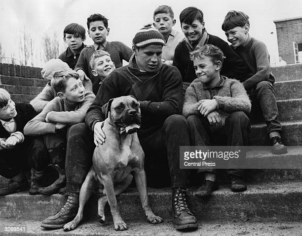 British world middleweight boxing champion Terry Downes with a group of young fans and his boxer dog 'Champ'