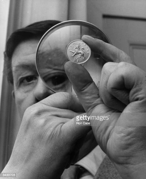 Christopher Ironside designer of the reverse side of the new decimal ten pence piece examines the coin through a magnifying glass at the Royal Mint