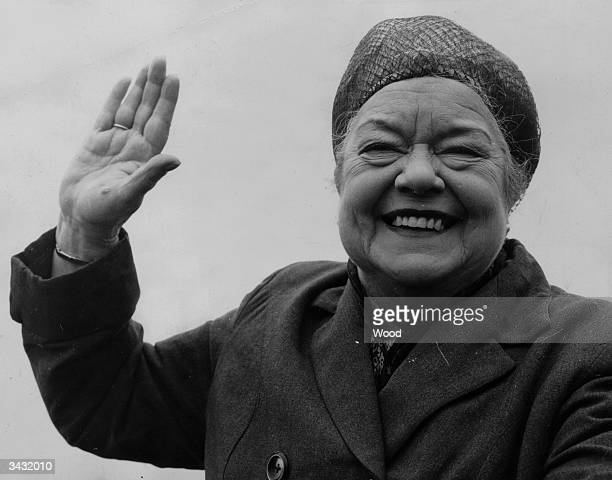 Wearing her famous hairnet actress Violet Carson in her costume as Ena Sharples from the ITV's 'soap' Coronation Street gives a cheery greeting