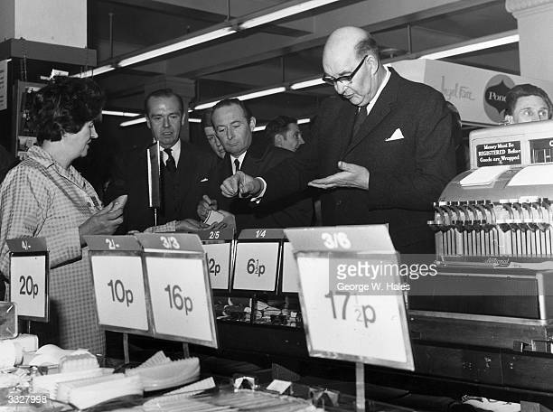 On the day of the official change to decimalised currency Lord Fiske chairman of the Decimal Currency Board makes a purchase at a Woolworths store in...